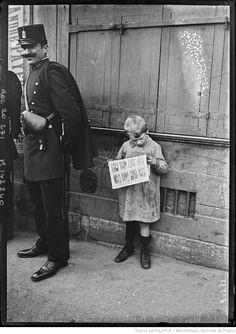 Le 1er mai [1912] à Paris, meeting de la rue de la Grange-aux-Belles [vue d'un enfant lisant un journal à côté d'un gardien de la paix] : [photographie de presse] / [Agence Rol]