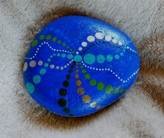 Painted stone with royal blue background and colourful by JulySea