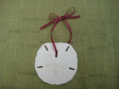 Paint a sand dollar with glitter glue to make a simple and elegant ornament. A fun craft to do with kids, to give as gifts or decorate presents with!