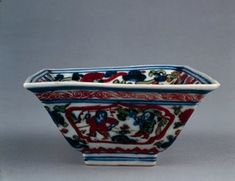 Square porcelain bowl with flared sides and everted rim. Wucai style with underglaze blue and overglaze red, green, aubergine and black enamels. Double square on inside centre enclosing a character, band of fungus scroll just below the rim. Red outlined panel on exterior with children at play in a landscape, with floral motifs. Classic scroll band in red at the rim, enclosed by blue parallel lines. Mark on base in underglaze blue. (Ming dynasty)
