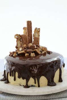 The ULTIMATE Peanut Butter & Fudgy Chocolate Overload Cake = two layers of moist chocolate mud cake smothered with the most delicious peanut butter frosting, drizzled with dark chocolate ganache and topped with Picnic bars, Flakes, Reeces Peanut Butter Cups, chocolate chips and peanut butter chips!! OMG this is one seriously over-the-top (and totally delicious!) cake.   #peanutbutter #fudge #chocolate #cake #ganache #thermomix #conventional