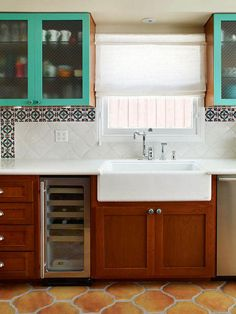San Felipe Saltillo tile flooring, a terra-cotta tile originating from Mexico, adds texture to this Spanish-style kitchen designed by Erica Islas. The eco-friendly floor tile by Arto neutralizes the teal cabinet and colorful, decorative Talavera tile backsplash.