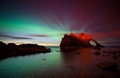 Northern Lights behind Bow Fiddle Rock, Moray, Scotland