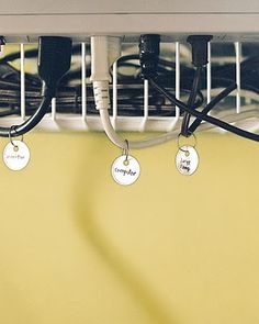Hide cords by hanging wire basket by 4 cup hooks under desk, adding a tag to label each one