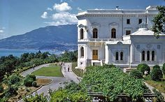 """livadia Palace showing how it looks over the Black Sea.  Tsar Nicholas II built this palace, replacing an earlier one, early in his reign.  Interestingly, after Nicholas was forced to abdicate in 1917, the Alexander Palace at Tsarskoe Selo became too dangerous for the Imperial Family so Nicholas petitioned the Provisional Government under Alexander Kerensky to allow him and his family to live quietly at the Livadia as private citizens. Kerensky refused and the rest is an historic tragedy."""