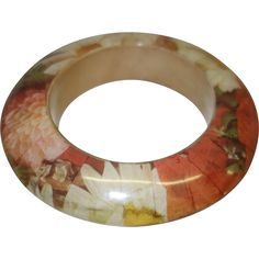 This is a vintage laminated wooden bangle bracelet.  It features a saucer-shaped wooden body laminated with flowers in orange,white and yellow---#vintagebeginshere at www.rubylane.com @rubylanecom #vintage #fallfashion