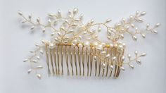 Inspired by the beauty of nature, this whimsical bridal hair comb would look stunning in the loose up-do of any modern, rustic bride!  The gold colour comb is approximately 7cm in length, and features wispy branches of ivory rice pearls nestled into bunches of different sized freshwater pearls. The branches are very flexible and can be manipulated into any shape you feel comfortable with.  Team with a simple veil or wear alone - both look great!  For the matching hair vine, please visit…