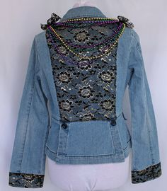 This is my Mardi Gras inspired jacket. This year Mardi Gras (Fat Tuesday) is February 21.  I applied a black and gold lace overlay on the back and cuffs of this blue princess style denim jacket. I added a few purple, gold and green mardi gras necklaces from previous celebrations for some kitschy fun. These are not attached. At both shoulders are lace epaulettes which tie to hold the beads on as shown...or not.  Strings of tiny seed beads are sewn on each of the front and back buttons.  Size…
