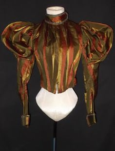 1890's striped BodiceThis exceptional bodice dates to the Victorian 1890's and is fashioned of a rich patterned striped French silk jacquard with massive balloon puffs atop the shoulders, fitted bottom sleeves with stiff buckram lined bottom cuffs trimmed in metallic braid and small shimmering sequins that matches the trimming of the high band collar. The collar hooks closed at a dart point, fully boned in the interior and lined in polished cotton.