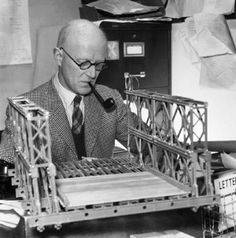 D C Bailey pipe in mouth sits in his office and examines the model of a Bailey bridge which is resting on his desk. UK Military Bridging Equipment (The Bailey Bridge)