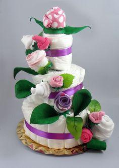 Maravillosa tarta de pañales y flores. Impresionante si quieres sorprender a los padres del bebé. Algo muy especial y precioso.  La ropa esta disponible en 2 tamaños y 2 temporadas.