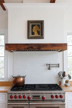 "KITCHEN – Brad Sullivan of Sullivan Building & Design Group shares the details of this custom wood hood: ""The fan itself is an insert by Broan with a roof-mounted remote blower. The enclosure was custom built with old beadboard paneling and antique wood beams."""