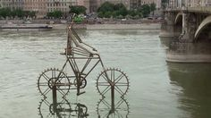 'danube bicycle' is a kinetic sculpture, created by zoltan kecskemeti  and installed in the danube river in budapest, hungary.    the piece brings together two kinds of environmentally friendly energy sources: man and water.  the flow of the river moves the wheels of the bicycle, which move the legs of the rider.