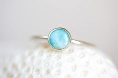 """Larimar is the embodiment of the tranquil Sea and Sky energies. Its soft, soothing blues and calming turquoise is streaked with white patterns that resemble sunlight dancing beneath Caribbean waters. It brings the ancient wisdom of Atlantis and the healing power of dolphins to harmonize the body and soul. Peridot has long been called """"an Evening Emerald,"""" for under the light, the stone glows a brilliant green. Peridot is similar to the emerald but softer in intensity. Peridots of two or…"""