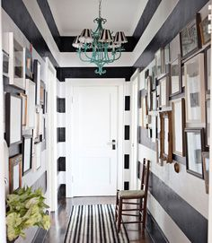A runner from Pine Cone Hill and a vintage chandelier, topped with Stray Dog shades, add to the striped effect.
