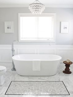 There is a lot I like about this whole picture. The simplicity, the soft palette. Would be nice with the modern version of the clawfoot. nice chandelier over the bathtub. I also like the pattern on the tile