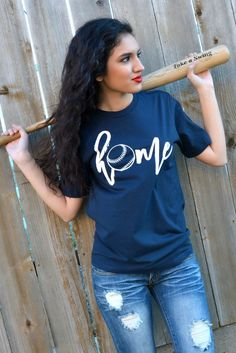 "Our Home Tee - Baseball Edition is a LaRue exclusive and features a navy blue super soft tee with the word ""home"" printed in white on the front with a baseball as the letter ""o"". Model is a size 2 and"