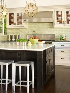 A light green backsplash adds refreshing color to this neutral kitchen. The classic subway tile shape blends with clean, traditional-style cabinetry, while the subtle hue lends modern flair. Brimming with views of the outdoors, the gentle green tiles also bring a touch of nature into the kitchen work space.
