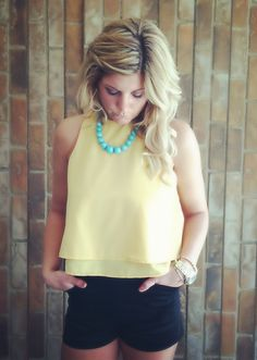 Yellow top paired with high waisted black shorts and blue necklace = soooo adorable!