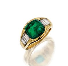 EMERALD AND DIAMOND RING, BULGARI.  The sugarloaf cabochon emerald highlighted with baguette diamond shoulders, to a yellow gold mount, size 52, signed Bulgari.