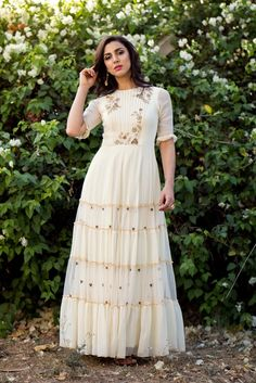 Embellished ivory tiered Anarkali set with net dupatta.Beautiful Long Dress with modern silhouettes and superb embellishments with embroidery . Indian Long Dress, Indian Gowns Dresses, Dress Indian Style, Casual Gowns, Stylish Dresses, Fashion Dresses, Dress Casual, Indian Designer Outfits, Indian Outfits