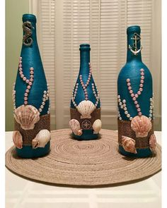 : This bottle is hand wrapped in teal thread and then decorated with real sea shells, faux pearls, mesh and metal emblem. It is perfect for any beach fanatic and sea lover, bringing the feel of the ocean into your home. **MADE IN AMERICA** Every bottle or Glass Bottle Crafts, Wine Bottle Art, Diy Bottle, Glass Bottles, Vodka Bottle, Empty Bottles, Wine Glass, Recycled Wine Bottles, Painted Wine Bottles