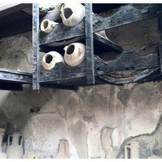En Herculano aún se conservan maderas carbonizadas, como este soporte para ánforas de vino, en esta taberna, sepultada por la lava durante la erupción del Vesubio. Se han conservado carbonizadas durante dos mil años. Italia.  #Esmadeco.