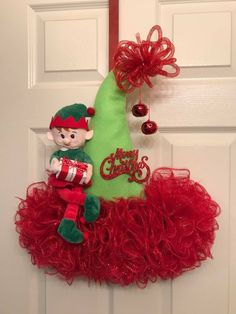 Super Fun DIY Christmas Decorations Ideas for Home – Mesh Wreath Elf hat made out of Store witchs hay I really like the look of the felt for the hat for clean lines The loopy ball on the top is a great touch Christmas Decorations For Kids, Christmas Crafts For Kids To Make, Christmas Mesh Wreaths, Christmas Projects, Holiday Crafts, Christmas Ornaments, Santa Wreath, Diy Christmas Hats, Christmas Door