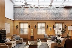 In this Tribeca penthouse, wood paneling in the style of architects and designers Jean Michel Frank, Adolf Loos and Bruno Paul is applied alongside Civil War-era bricks and neutral-toned, geometric furniture. Photo courtesy Triarch.
