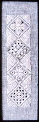 """Intermediate Level Diamonds is the second in a series of three designs which all use the same diamond layout. Stitch the design as shown or use the individual diamonds for ornaments or on other whitework projects. Stitch count is 60 x 240 with a design size of 2.125"""" x 8.5"""". Supplies required:  28-count White Cashel (3281-100)   DMC Size 8 Pearl Cotton: White"""