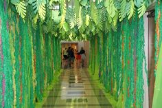 Attached vines (strips of plastic tablecloth pulled) to plastic tablecloths and hung them from the ceiling tiles. Added cut leaves to each metal divider on the drop ceiling. Jungle Theme Classroom, Jungle Theme Birthday, Wild One Birthday Party, Jungle Party, Safari Party, Safari Theme, Ceiling Decor, Ceiling Ideas, Jungle Decorations