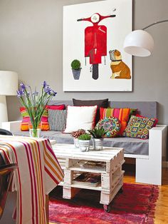 Mesa de palets y almohadones de colores. Un apartamento fresco y juvenil para estudiantes