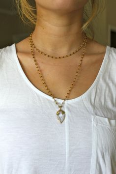 Dark gray beads on a gold chain with gold rimmed quartz arrowhead