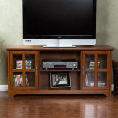 This Mission Oak TV Stand - Fits up to 50-inch Flat Screen TV features a rustic charm with a contemporary style with tempered glass doors. This stand fits up to a 50-inch flat panel TV and showcases a