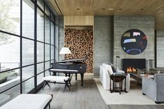 A view of a seating area with a fireplace and piano—and an ample supply of firewood.