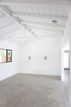 polished concrete, white walls, exposed beams, black frames