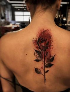 A rose tattoo located on the back around the spine. The rose is a long straight one, with the petal around the neck and the stem running down to the midsection of the back. The ink is simple and dark, but the whole top area, with the petals and its surroundings inked red. #tattoofriday #tattoos #tattooart #tattoodesign #tattooidea