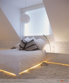 Double bed and sideboard with integrated, indirect lighting in modern attic room | © living4media | View Pictures | 11029230