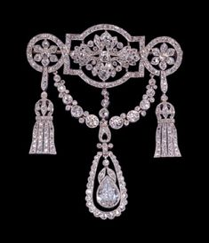 Platinum mille-grain and diamond pendant brooch, the centre rectangle with curved top and base flanked by circles enclosing respectively a large foliate ornament and six-pettalled rosettes, hung with a chain of collet set stones terminating in a pear shaped drop swinging within an open chain border with a diamond swag terminating in tassels linking the two circular elements. C.1910.