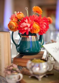 Red and orange wedding flowers in dark teal tea pot! Such a cute idea!