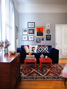 Blue velvet couch gray walls molding and white paint oriental rug, two end tables as coffee table