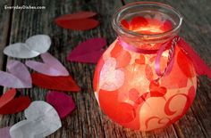 Make a heart lantern to decorate for Valentine's Day. Cut hearts out of tissue paper, glue them on a jar then insert lights to set the mood.