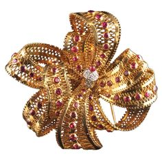 brooch designed as 18ct gold 'lace' tied in an elaborate bow and set with rubies to a central diamond and ruby stigma. Van Cleef & Arpels, Paris 1939