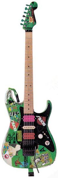 """Steve Vai's Electric """"The Green Meanie"""" No Serial Number The """"Green Meanie"""" is actually a Charvel Strat-style guitar loaned to Steve by Grover Jackson (of Jackson Guitars) when Steve joined Alcatrazz. Originally a sunburst finish, Steve stripped it and painted it day-glo green, and it has eventually become covered in various stickers, etc. This guitar was used on """"Disturbing The Peace"""" and for virtually everything on """"Eat 'Em & Smile"""". It has since been retired and is safely locked away."""