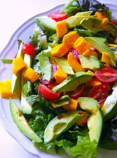 Caribbean Salad-really pretty salad with tomatoes, mango, avocados, mix greens and a easy and delicious dressing. any fruit or veggie substitutions are fine with this recipe!