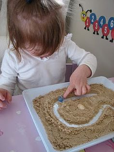 Pre-writing in sand.  Draw simple letter in sand and put one marker at the start and one at the end.  Encourage child to trace the path and help one marble find the other.