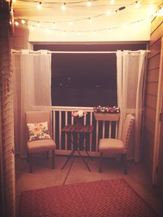 Small apartment patio with lights strung at night <3