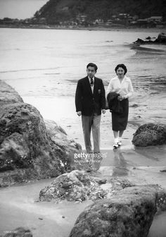 Crown Prince Akihito Of Japan and Crown Princess Michiko walk on a beach in April 1959 in Hayama, Japan.