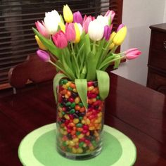 Fill mason jar with jelly beans and top with tulips to great this colourful centrepiece for easter!