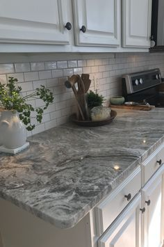 Fantasy Brown granite with small white subway tiles and warm gray grout.